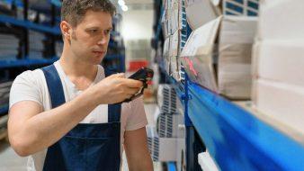 Operatore in un magazzino legge un codice a barre con un terminale portatile