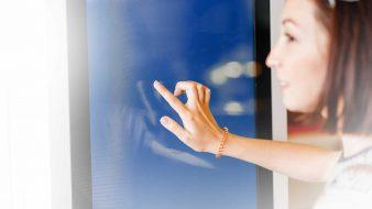 Ragazza tocca lo schermo di un totem touch screen